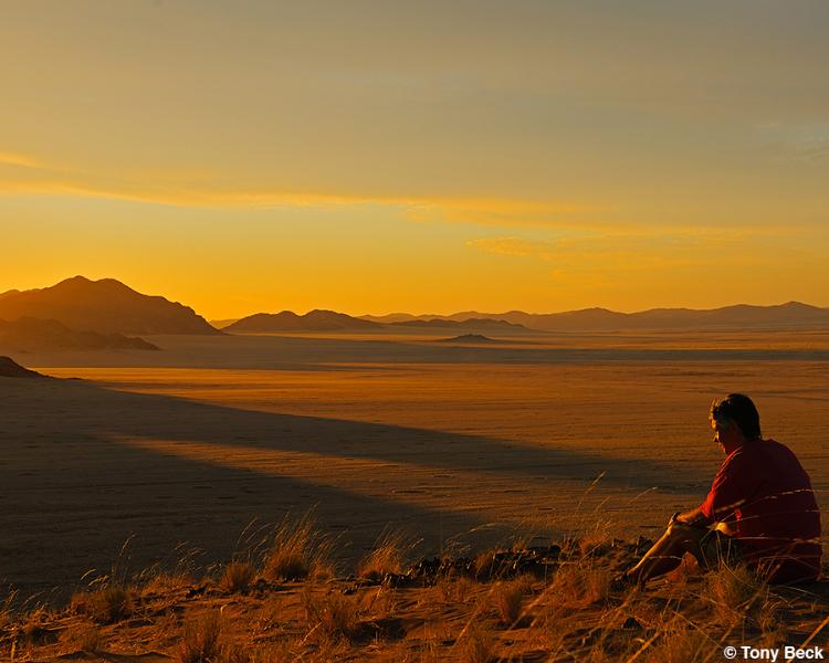 Allison relaxing as amber sun rays shine on a golden Namibian desert